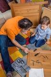 Fader och son som monterar ett nytt möblemang för hem Royaltyfri Foto