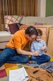 Fader och son som monterar ett nytt möblemang för hem Royaltyfri Bild