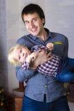 Fader och son som omkring bedrar på julgranen med gåvor Royaltyfria Bilder