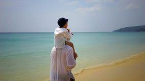 Fader och son som på fötter går längs stranden nära havet Arkivbilder