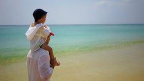 Fader och son som på fötter går längs stranden nära havet Arkivfoto