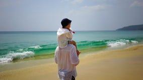 Fader och son som på fötter går längs stranden nära havet Arkivfoton