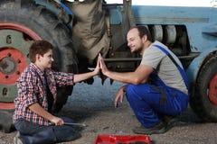Fader och son som reparerar en traktor Arkivbilder