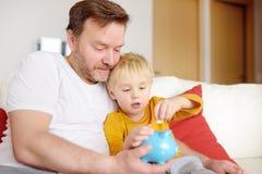 Fader och son som s?tter myntet in i spargrisen Utbildning av barn i finansiell l?s-och skrivkunnighet royaltyfri fotografi