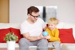 Fader och son som s?tter myntet in i spargrisen Utbildning av barn i finansiell l?s-och skrivkunnighet arkivbilder