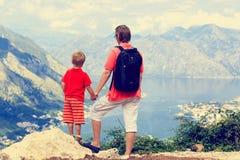 Fader och son som ser berg på semester Arkivbild