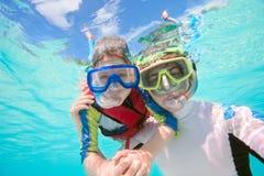Fader och son som snorkeling Arkivbild