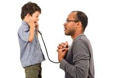 Fader och son som spelar doktorer Arkivfoton