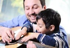 Fader och son som spelar gitarren royaltyfri bild