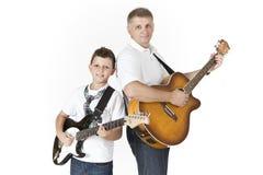 Fader och son som spelar gitarrer Arkivfoton