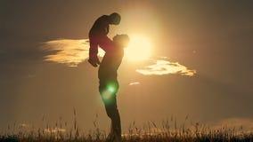 Fader och son som spelar i parkera på solnedgångkonturn av en lycklig familj lager videofilmer