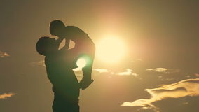 Fader och son som spelar i parkera på solnedgångkonturn av en lycklig familj arkivfilmer