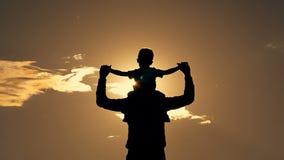 Fader och son som spelar i parkera på solnedgångkonturn av en lycklig familj stock video