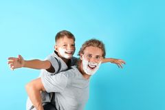 Fader och son som spelar med att raka skum på framsidor mot färgbakgrund royaltyfri bild