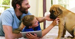Fader och son som spelar med en hund