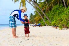 Fader och son som spelar med flygdisketten på stranden Royaltyfria Bilder
