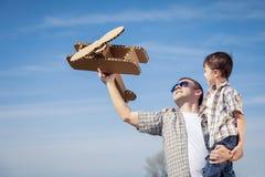 Fader och son som spelar med pappleksakflygplanet i parkera a Royaltyfria Foton