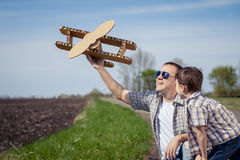 Fader och son som spelar med pappleksakflygplanet i parkera a Arkivbild