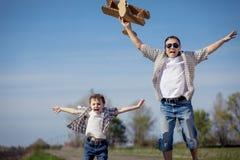 Fader och son som spelar med pappleksakflygplanet i parkera a Arkivfoton