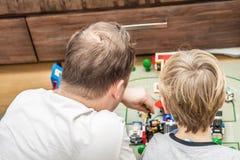 Fader och son som spelar med plast- kvarter royaltyfri foto