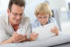 Fader och son som spelar med smartphonen och minnestavlan Arkivbild