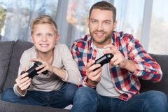 Fader och son som spelar med styrspakar Arkivbild