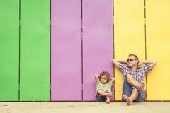 Fader och son som spelar nära huset på dagtiden Royaltyfria Bilder