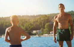 Fader och son som spelar på bachen nära havet Man och pojke mot havet, aktiv semester för sommarferie, disigt sommarljusfoto Royaltyfri Foto