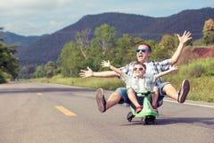 Fader och son som spelar på vägen royaltyfri bild