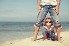 Fader och son som spelar på stranden på dagtiden Arkivfoton