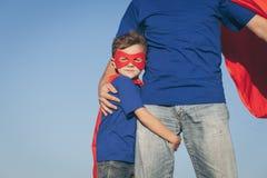 Fader och son som spelar superheroen på dagtiden royaltyfri bild