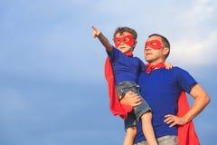Fader och son som spelar superheroen på dagtiden Arkivfoto