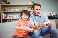 Fader och son som spelar videospelet, medan sitta på soffan Arkivbild