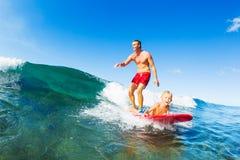 Fader och son som surfar och att rida vågen tillsammans Royaltyfria Bilder