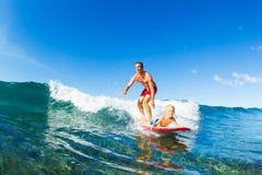 Fader och son som surfar och att rida vågen tillsammans Royaltyfri Foto