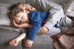 Fader och son som ta sig en tupplur på soffan Fotografering för Bildbyråer