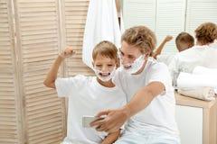 Fader och son som tar selfie med att raka skum arkivfoton