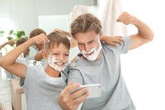 Fader och son som tar selfie med att raka skum på framsidor arkivfoto