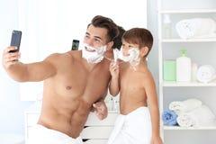 Fader och son som tar selfie, medan raka arkivfoton