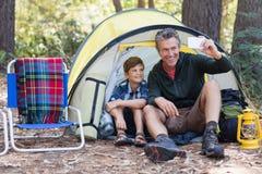 Fader och son som tar selfie, medan sitta i tält Royaltyfri Bild