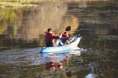Fader och son som tillsammans kayaking på en sjö, baksidasikt arkivfoton