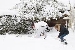 Fader och son som tillsammans skyfflar snö i en trädgård Royaltyfri Bild
