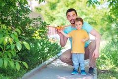 Fader och son som tillsammans utomhus spelar i sommardag: farsan och barnet lanserar leksakflygplanet Ny start, föräldra- hjälpbe fotografering för bildbyråer