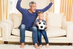 Fader och son som triumferar på soffan Royaltyfri Bild