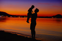 Fader och son som tycker om liv på solnedgången Arkivfoton