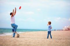 Fader och son som tycker om sommarsemestern som spelar strandaktivitetslekar nära havet, familj som kastar flygskivan arkivfoton