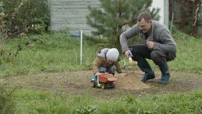 Fader och son som utomhus spelar. stock video