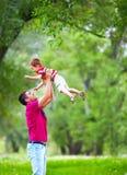 fader och son som utomhus spelar i vårskog royaltyfri fotografi