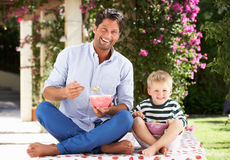 Fader och Son som utomhus tycker om frukostsädesslag Royaltyfria Foton