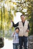 Fader och son som visar fiskelåset på sjön Arkivfoto